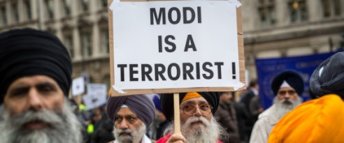 LONDON, ENGLAND - NOVEMBER 12: A protestor demonstrating against Indian Prime Minister Narendra Modi holds a placards outside Downing Street on November 12, 2015 in London, England. Modi began a three-day visit to the United Kingdom today which will be marked by a speech to Parliament a meeting with the Queen and an address to crowds at Wembley Stadium. (Photo by Rob Stothard/Getty Images)