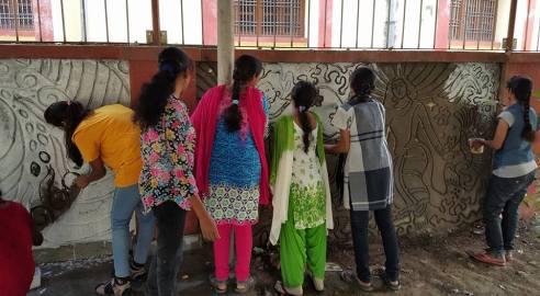 women painting mural